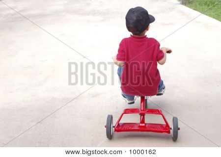 Boy Riding A Tricycle