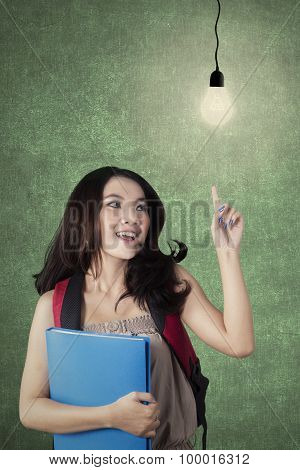 Clever Female Student Pointing At Light Bulb