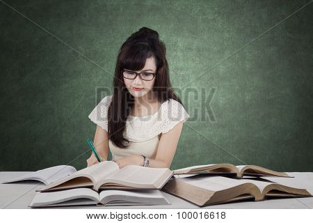 College Student Doing Assignment In The Class