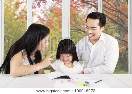 Father And Mother Advising Their Kid To Learn