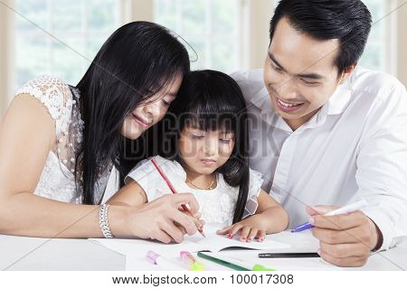 Friendly Parents Help Their Kid Wrote On The Book