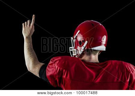 Rear view of american football player triumphing against black background