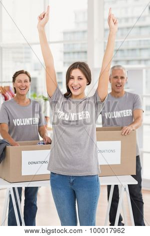 Portrait of cheering female volunteer in front of colleagues in the office