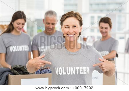 Portrait of smiling female volunteer pointing on shirt in the office