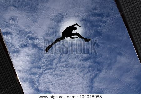 Man Jumping Over Building Roof