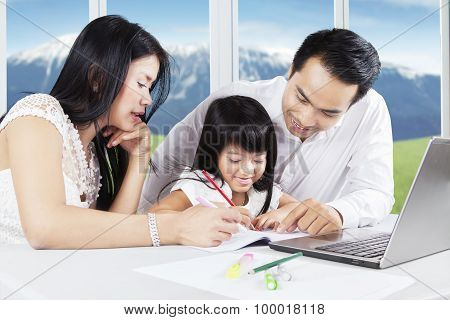 Happy Girl Learning With Her Parents