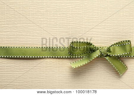 Green ribbon bow on golden paper textured  background