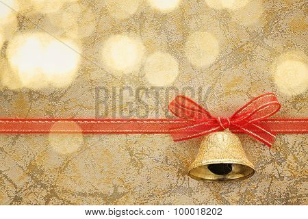 Golden jingle bell with ribbon bow on festive background