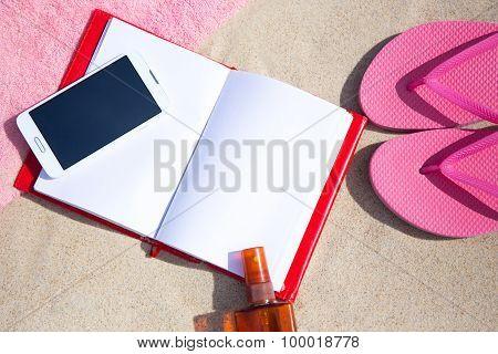 Summer Concept - Flip Flops, Towel, Phone, Book And Suntan Lotion Bottle On Sandy Beach