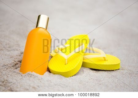 Summer Concept - Slippers And Suntan Lotion Bottle On Sandy Beach