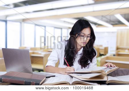 Student Doing School Assignment In The Class