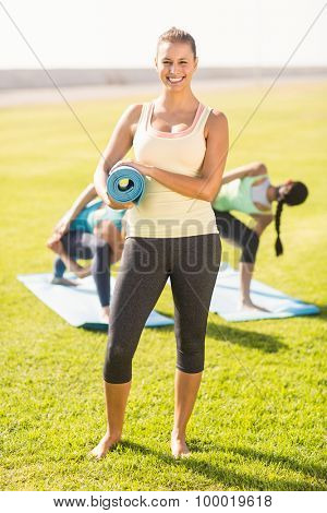 Portrait of smiling sporty brunette in front of friends doing exercises in parkland