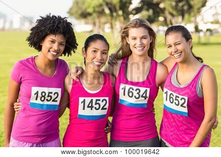 Portrait of four smiling runners supporting breast cancer marathon in parkland