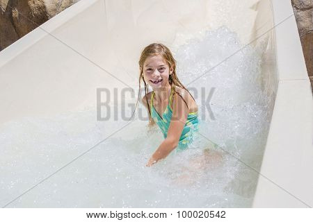 Cute little girl riding down a water slide at a water park