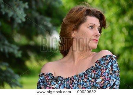 woman in a dress with open shoulders at  pine forest