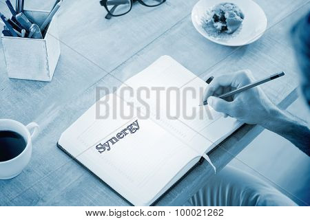 The word synergy against man writing notes on diary