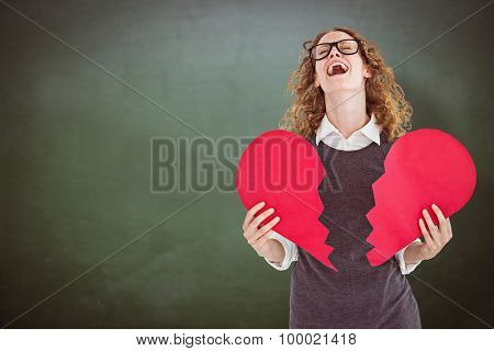 Geeky hipster holding a broken heart card against green chalkboard