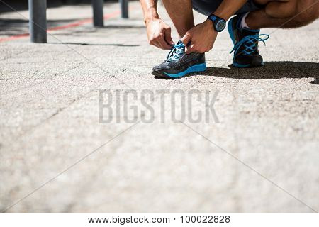Low angle view of an athletic man tying his shoe laces