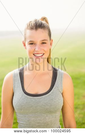 Portrait of smiling sporty blonde looking at camera in parkland