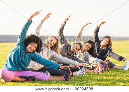 Portrait of smiling sporty women stretching during fitness class in parkland