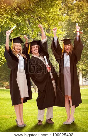 Three students in graduate robe raising their arms against trees and meadow