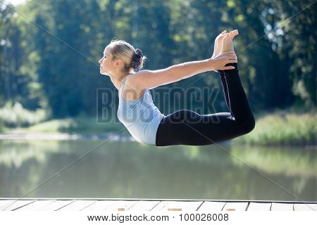 Yogi Female Doing Bow Pose In Mid Air