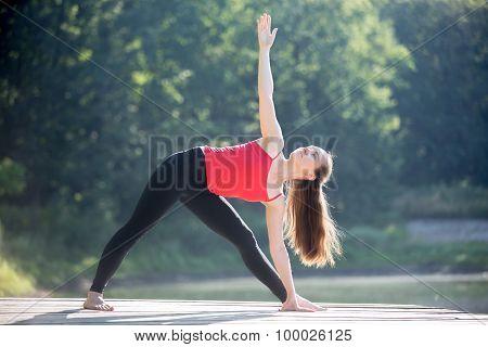 Teenage Girl In Utthita Trikonasana Pose