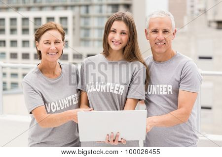 Portrait of smiling volunteers with laptop on roof of building
