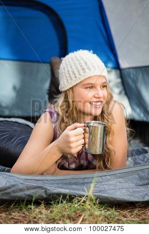 Pretty blonde camper smiling and lying in tent in the nature