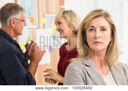 Stern businesswoman ahead with her team behind at office