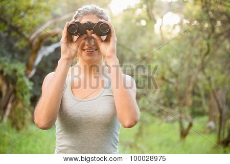 Smiling pretty brunette looking through binoculars in the nature