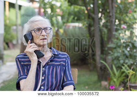 Ninety Years Old Lady Talking On The Phone In The Backyard
