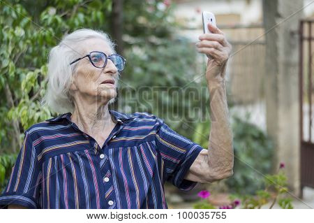 Ninety Years Old Grandma Taking A Selfie With A Smartphone In The Backyard