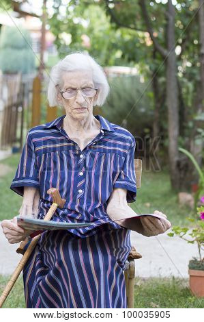 Ninety Years Old Lady Reading The Newspapers In The Backyard