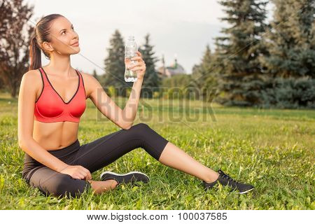 Cheerful young sport girl is resting in park after training