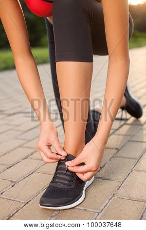 Cheerful young female athlete is preparing for jogging