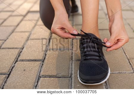 Pretty young sportswoman is fixing her running shoes
