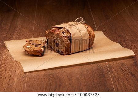Sliced fruit bread with raisins prunes and nuts in baking paper on dark wooden table