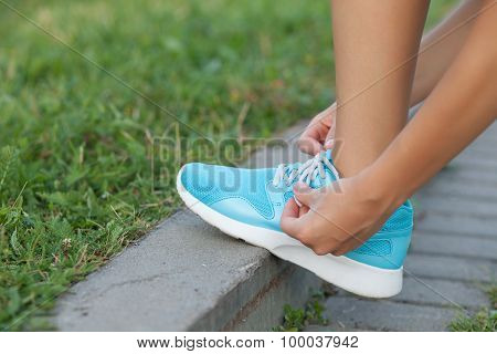 Young woman is fixing laces of her running shoes