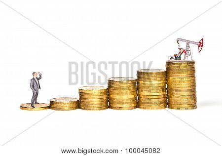 Businessman Standing On A Stack Of Coins With The Oil Pump, The Oil Crisis Concept