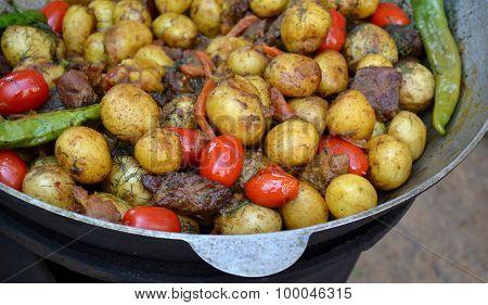 Big cauldron with roasted potato, meat and tomato