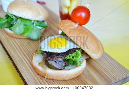 Two cute mini burgers with fried eggs