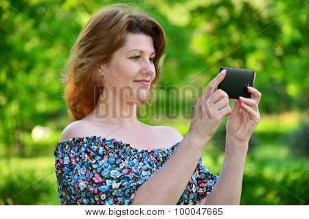 woman with a cell phone in pine park