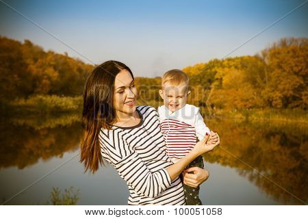 Portrait Of Smiling Mother And Baby On Lake