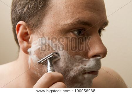 Man Shaving His Cheek
