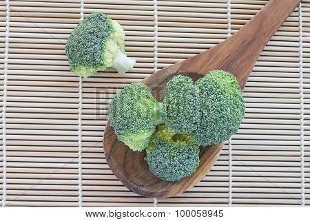 Fresh Broccoli Vegetable In Wooden Spoon On Mat Bamboo