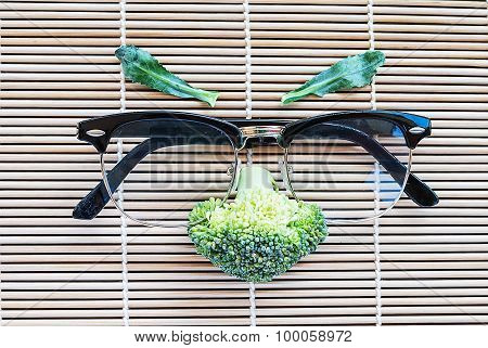 Face Of Fresh Broccoli With Glasses On Pattern Bamboo For Background