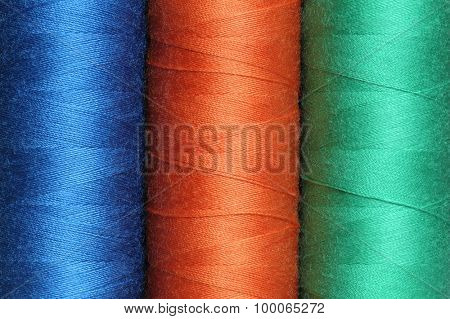 Three spools of color polyester threads closeup