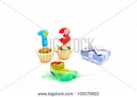 Cakes With Thirteen Years Birthday Candles, Whistle And Gift On White