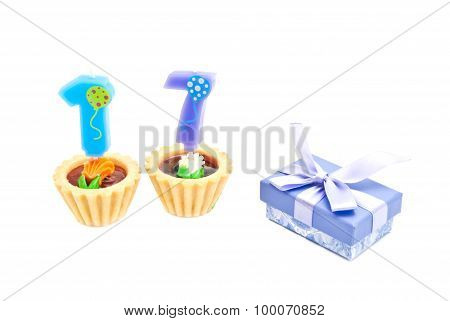 Cakes With Seventeen Years Birthday Candles And Gift On White